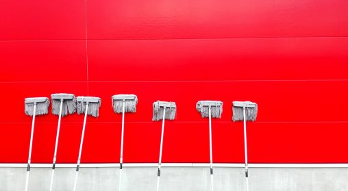What to Look For in a Commercial Cleaning Company. Mops leaning against a red wall